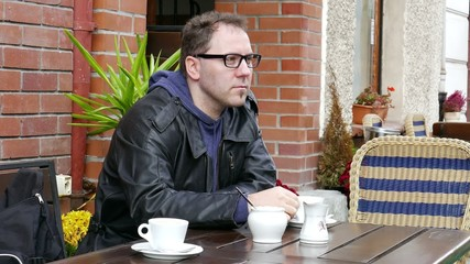 Seriously looking, pensive man drinks coffee in the cafe