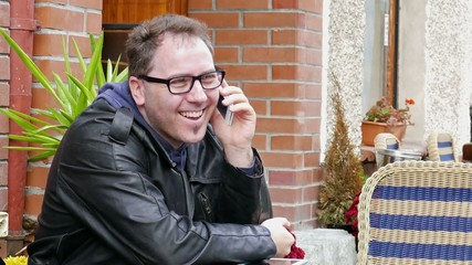 Happy, smiling man in glasses is talking on a mobile phone