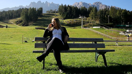 Happy business woman relaxing in the mountain on the phone