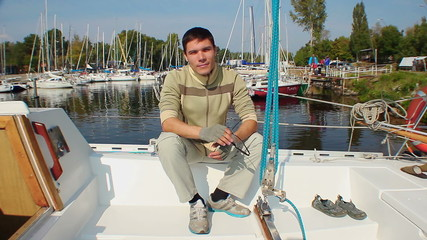 Portrait of positive young man on sailboat in marina, yachting