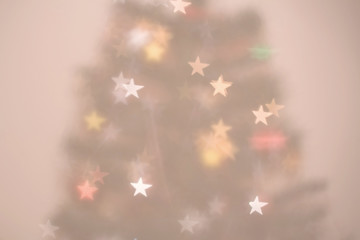 Christmas tree defocused background with star-shaped bokeh.