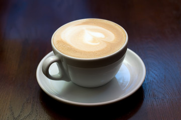 The cup of cappuccino at the table