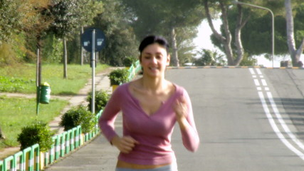 Medium shot of beautiful woman jogging on street