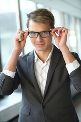 young businessman with glasses standing in the hallway