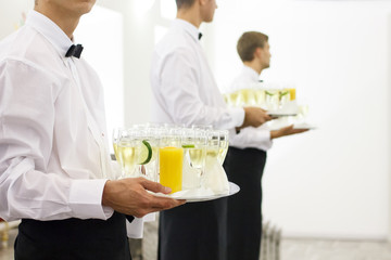 Three waiters in bow ties holding trays of champagne in glasses.