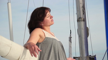Happy smiling woman relaxing on sailing yacht, meditation