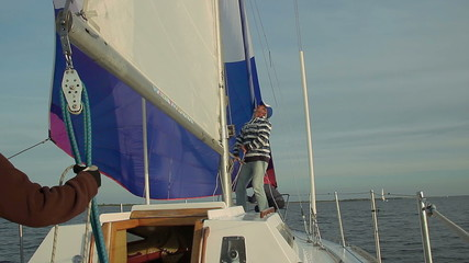 Captain putting up mainsail on beautiful yacht, traveling