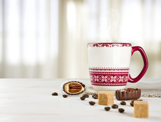 Hot coffee cup on table over blurred curtained window background