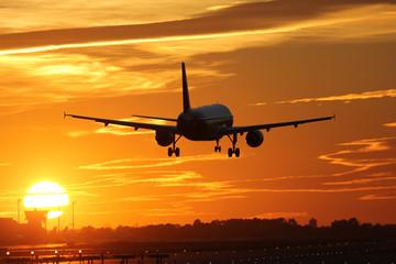 Flugzeug beim Landen auf Flughafen mit Sonnenuntergang