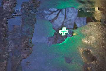 green cross reflection in rain puddle