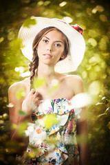 Young beautiful brunette woman wearing a large hat