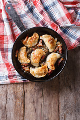 fried dumplings with onion and bacon in a pan vertical top view