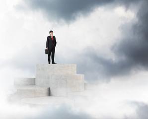 businessman standing on peak stairs