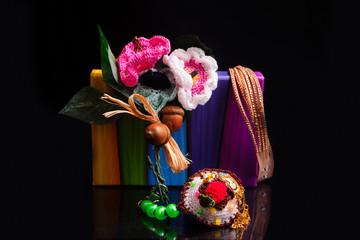 Fiori e gioielli su scatola colorata, sfondo nero