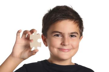 bambino sorridente mostra pezzo di un puzzle