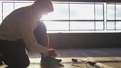 Hooded man tying his laces before a workout outdoors