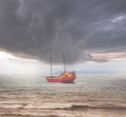 Sailing vessel in the stormy sea near the island.