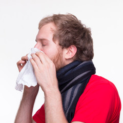 Man with runny noses neezes into a tissue
