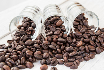 Coffee beans in a glass on wooden background