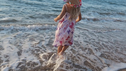 Little girl full of emotions walking along the seashore with her