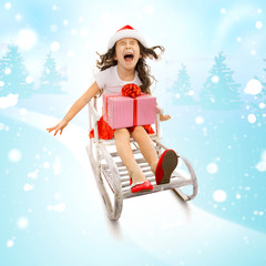 Girl with Christmas gift box on a sled