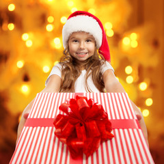 Child holding Christmas gift box in hand.