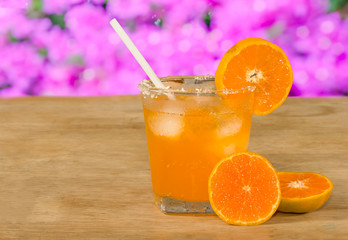 Glass of orange juice and fresh orange  on wooden table,pink bok