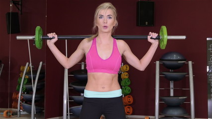 Woman doing shoulder exercise with a weight bar in a gym.