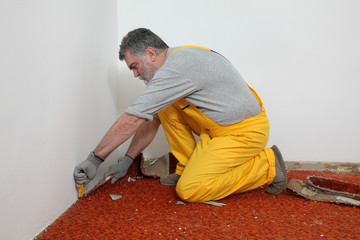 Home renovation, worker remove carpet from room floor