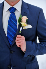 rose boutonniere on suit of the groom
