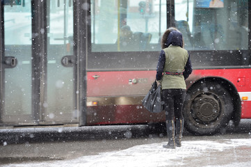 Woman waiting for bus in snow storm