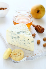 Blue cheese with almonds, figs and honey on a cutting board