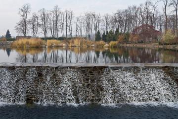 Autumn on the park pond with cascade