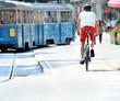 Bike commuter and tram in sunlit city - 75229348