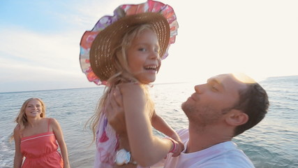 Father picks up the little daughter in straw hat while standing