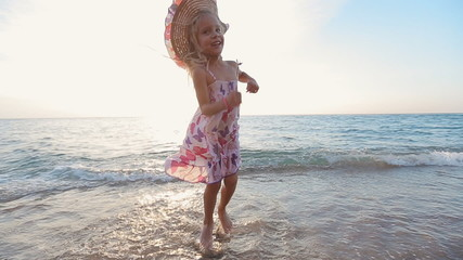 Little girl jumping in the sea water and runs to father