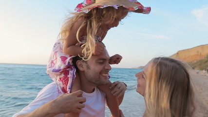 Laughing parents with little daughter sitting on the neck of