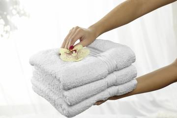 Frauenhände bieten einen Stapel Badetücher an