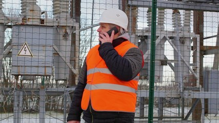 Electrical Engineer talking on cell phone in  substation