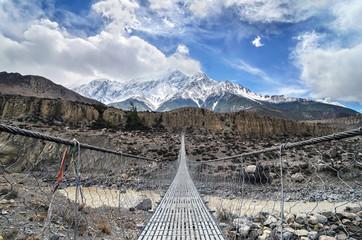 Suspencion bridge across the mountain river in Himalayas