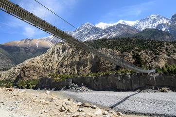 Suspension bridge across the river in mountains