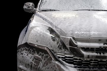 Modern car covered by foam. Car wash.
