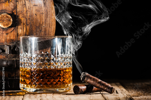 Foto op Aluminium Bar Glass of alcohol and smoking noble cigar on a black background