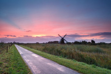 purple sunrise over Dutch farmland with windmill