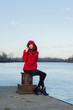 Beautiful lady sitting on the dock beside river on cold autumn d