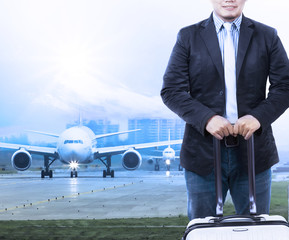 young man and traveling luggage staning in front of air plane ta
