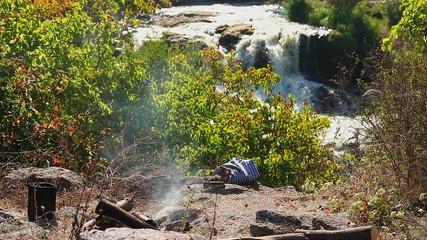 Camping near waterfall, smoke hovering above traveler's campfire