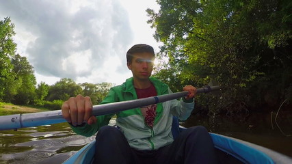 Young happy male paddling kayak, extreme sports
