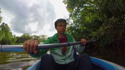 Handsome smiling man kayaking, action camera, summer, tourism