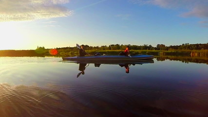 Two men boating on river at sunset, tourism, vacation, slow-mo